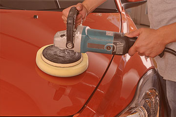 auto technician buffing an automobile after a vehicle collision